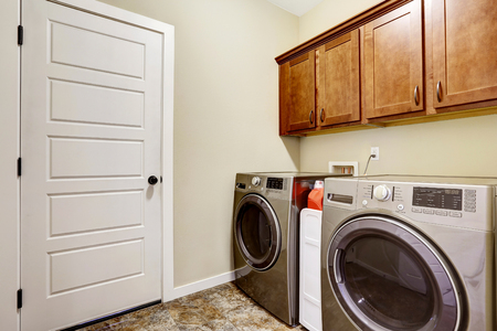 laundry room: Laundry room with steel appliances and nice cabinets, tile floor and beige walls