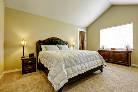 master bedroom: Master bedroom with deep brown furniture set and vaulted ceiling. Beige carpet floor with pastel yellow walls. Stock Photo