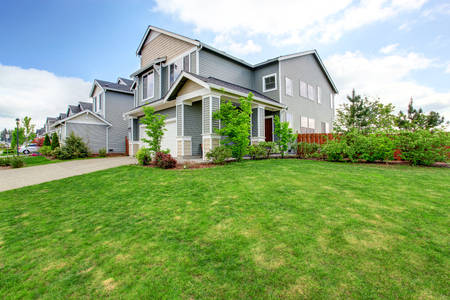 curb: Beautiful curb appeal of large blue house and green front yard with well kept lawn.
