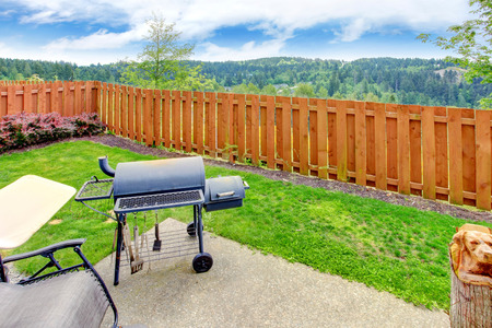 areas: Fenced backyard with concrete patio area and barbecue. Beautiful landscape Stock Photo