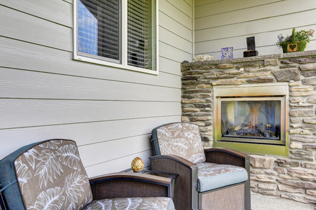 stone fireplace: Cozy sitting area with two comfortable armchairs and fireplace with natural stone decor. House exterior.