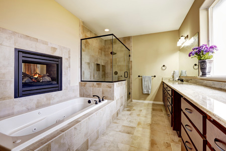 master bath: Master bathroom in modern house with fireplace, bath tub with tile trim, glass shower and modern cabinets.