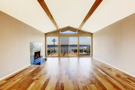 the vaulted: Empty room interior with hardwood floor, vaulted ceiling and fireplace with tile trim. Glass doors leading to the balcony