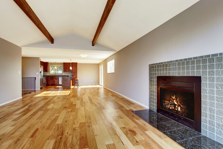 vaulted ceiling: Empty room interior with hardwood floor, vaulted ceiling and fireplace. View of kitchen room. Stock Photo