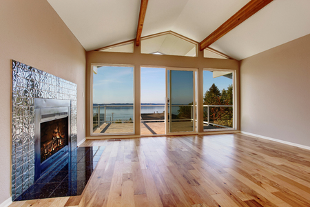 glass doors: Empty room interior with hardwood floor, vaulted ceiling and fireplace with tile trim. Glass doors leading to the balcony