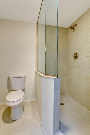bagno interno bianco con piastrelle beige, doccia in vetro e servizi igienici.