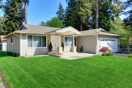 Américaine beige extérieur de la maison avec un parement. Vue de petit porche avec des colonnes et la porte d'entrée blanc.