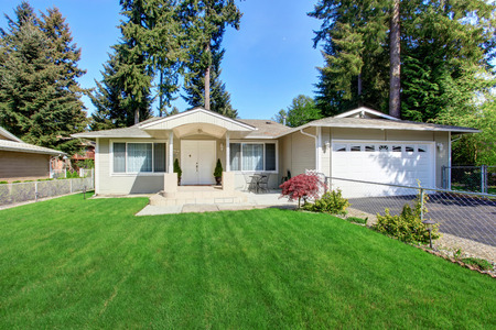 curb appeal: Curb appeal of beige house with well kept lawn and garage with driveway Stock Photo