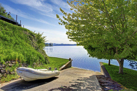 Beautiful landscape with concrete floor way to the water for boat launching. House exterior.