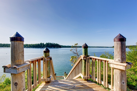 House exterior. Awesome water view from the wooden staircase with railings.