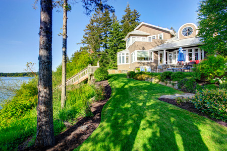 Luxury house exterior with impressive backyard landscape design, patio area and water view.