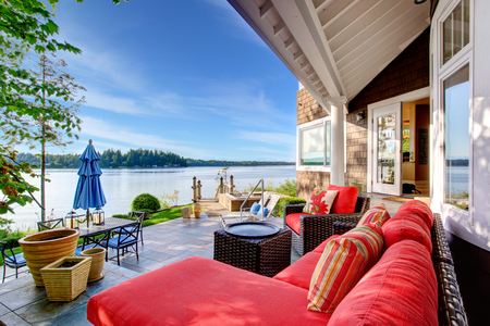 red pillows: Luxury house exterior with impressive water view, cozy patio area and sitting place with wicker sofa and red pillows. Stock Photo