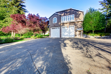 concrete floor: Luxury gray house with white trim and two garage spaces with concrete floor driveway. Stock Photo