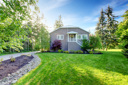 house with style: Gray large house exterior with green back yard with trees and well kept lawn, also driveway. Stock Photo