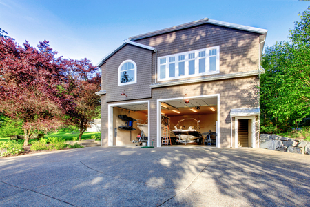 white trim: Luxury gray house with white trim and two motor boats in garage. Spacious driveway with concrete floor.