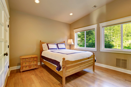 Simple beige bedroom interior with light brown nightstand, hardwood floor and two windows.