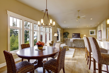 vaulted ceiling: Open plan interior with lots of space. View of dining room and living room. Has vaulted ceiling, hardwood floor and large six pane window. Stock Photo