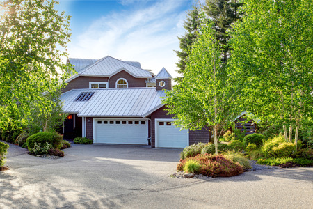 curb: Modern large house exterior with curb appeal. View of garage and concrete floor driveway