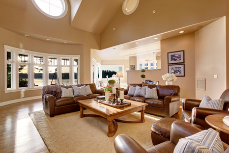 furnished: Large living room interior design with high vaulted ceiling, brown leather sofa set and lots of sunshine. Stock Photo