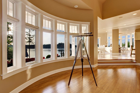 living room window: Interior of large living room with telescope by large six pane window. View of dining area. Stock Photo