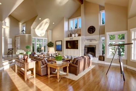 Grand design d'intérieur salon avec haut plafond voûté et cuir canapé. A télescope par la fenêtre