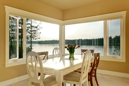 designer chair: Dining room interior with white table set and tile floor. Windows overlooking water view. Stock Photo