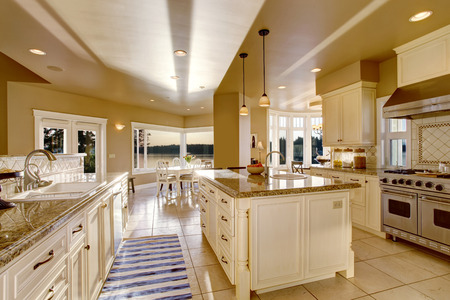 Large luxury kitchen room in beige colors with granite counter tops and kitchen island. View of dining area