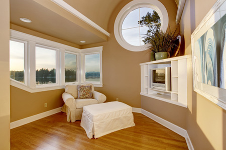 sitting area: Cozy sitting area upstairs with comfortable armchair and TV set in the corner. Water view. Stock Photo