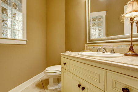 yellow walls: Cozy bathroom interior with decorative lamp on old white cabinets,  yellow walls and toilet.