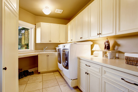 laundry room: White laundry room interior with tile floor and cabinets. House interior.