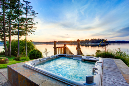 Geweldig uitzicht op het water met een hot tub in de zomer 's avonds. Huis exterieur.