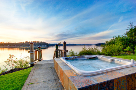 hot tub: Awesome water view with hot tub at dusk in summer evening. House exterior.