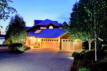 Lovely curb appeal of large luxury house with blue roof. Summer evening.