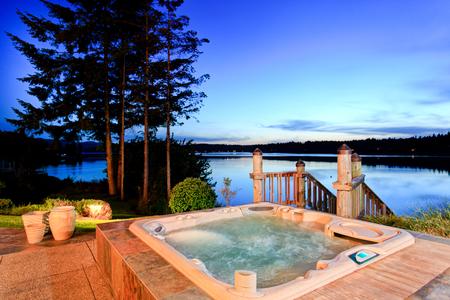 Geweldig uitzicht op het water met een hot tub in de schemering in de zomer 's avonds. Huis exterieur. Stockfoto