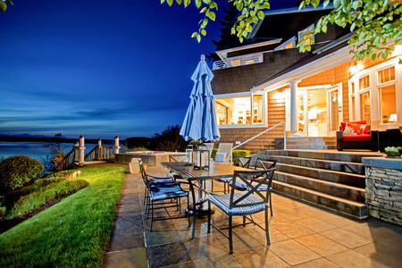 Luxury house exterior with impressive water view and cozy patio area. Summer evening. 版權商用圖片