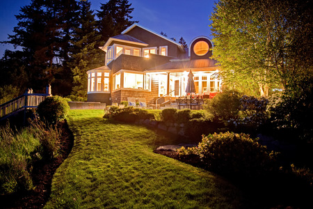 two story: Large two story house with lots of lights in the summer evening. View of backyard garden with lawn.