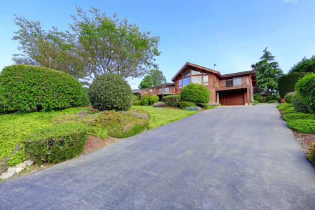 trim: Large wooden trim house with walkway, garage and lots of grass. Water view