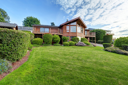 Large wooden trim house with walkway, garage and lots of grass. Zdjęcie Seryjne