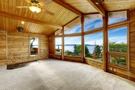 balcony door: Empty living room with carpet floor in wooden trim house with large windows and balcony door. Water view