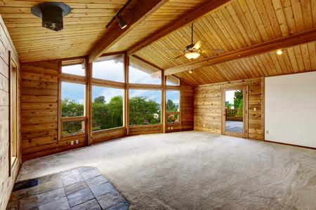 balcony door: Empty living room with carpet floor in wooden trim house with large windows and balcony door Stock Photo