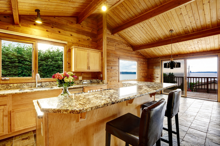 kitchen counter top: Wooden trim home with open floor plan. Kitchen with granite counter top. Water view Stock Photo