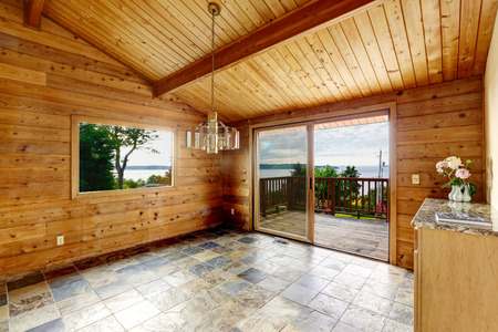 balcony: Empty room with tile floor and wooden trim. Opened balcony door. Way to deck and patio area with water view Stock Photo