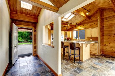 Pasillo con la puerta abierta y el suelo de baldosas. Ver al patio trasero. cocina abierta. adornos de madera Foto de archivo