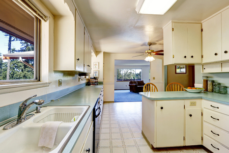 cocina vieja: Blanca vacía sencilla cocina antigua conectado a la sala de estar en la casa histórica de América. Foto de archivo