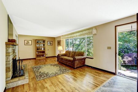 room door: Old American house large living room interior with hardwood floor, rug and fireplace. Open door to backyard
