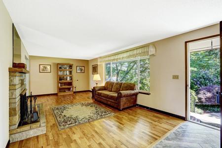 floor rug: Old American house large living room interior with hardwood floor, rug and fireplace. Open door to backyard