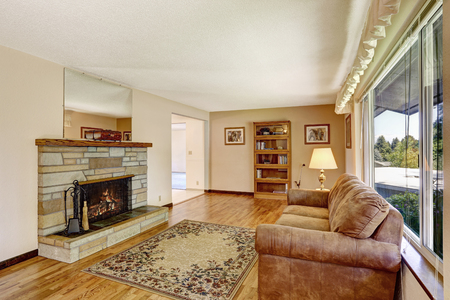 floor rug: Old American house large living room interior with hardwood floor, rug and fireplace.