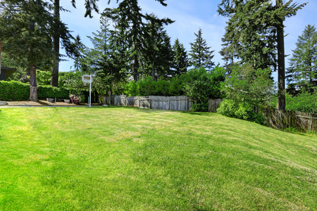 lawn area: Spacious backyard area with wooden fence, green lawn and basketball court Stock Photo