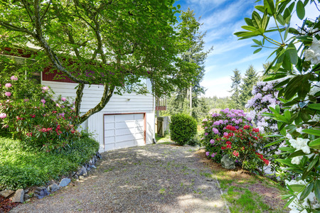 garage on house: House exterior. View of garage and driveway. Around blossom flowers Stock Photo