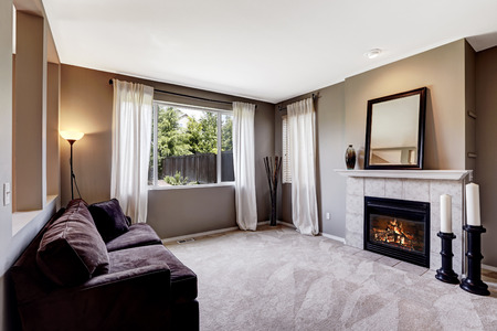 fireplace living room: Living room interior with carpet floor, fireplace and dark sofa